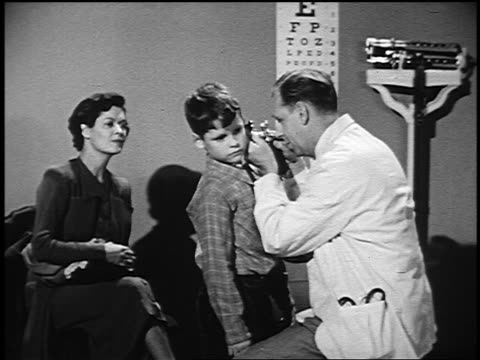 B/W 1950 woman watching as doctor uses otoscope to look in boy's ears in examining room