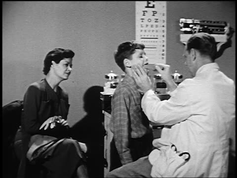 B/W 1950 woman watching as doctor uses tongue depressor to look at boy's throat in examining room