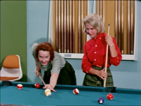 vídeos de stock e filmes b-roll de 1963 woman watching as other woman shoots pool / they both smile / industrial - mesa de bilhar