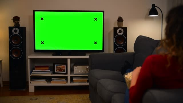 vídeos de stock e filmes b-roll de woman watching chroma key green screen tv at home - controlo remoto