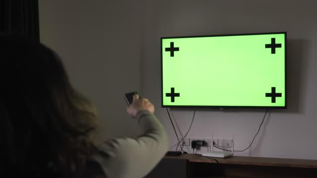 vídeos de stock, filmes e b-roll de croma de mulher assistindo tv e mudando de canal em casa-chave - indústria televisiva