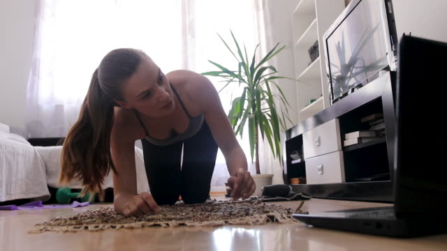 woman watching exercise tutorial on laptop and doing plank in living room at home - exercise room stock videos & royalty-free footage