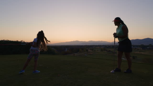 woman watching girl teeing off then high-fiving her at sunset / cedar hills, utah, united states - daughter stock videos & royalty-free footage