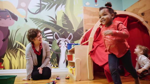 Woman watching girls playing at daycare