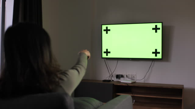 Woman Watching Green screen TV and changing channel at home