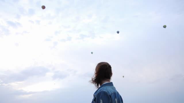 vídeos de stock e filmes b-roll de woman watching hot air balloons flying in the sky. - distante