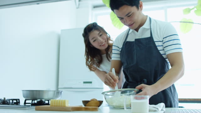 Woman Watching Man Making Food in Domestic Kitchen
