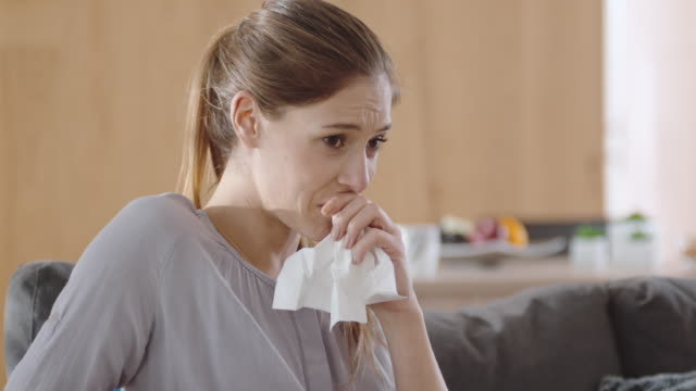 Woman watching something sad on the TV and crying