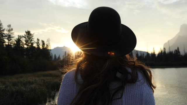 A woman watching sunrise over Vermillion Lakes in Banff National Park.