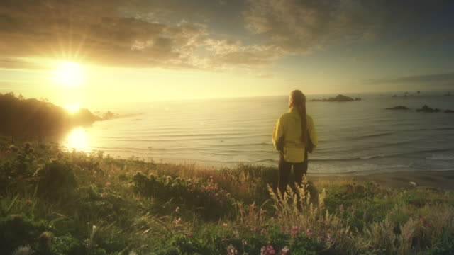 MS SLO MO POV Woman watching sunset on Pacific Ocean / Cape Blanco, Oregon, United States