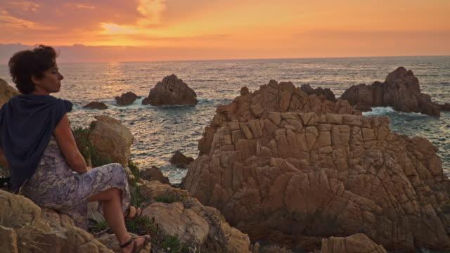 vídeos de stock e filmes b-roll de woman watching the sunset in costa paradiso - só mulheres de idade mediana