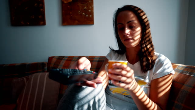 woman watching tv and drinking coffee - laziness stock videos and b-roll footage
