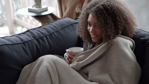 vídeos de stock, filmes e b-roll de mulher assistindo tv, cobrindo-se com um cobertor e beber café em uma manhã fria de inverno - assistir tv