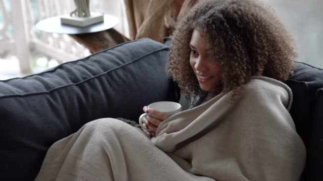 woman watching tv covering herself with a blanket and drinking coffee in a cold winter morning - guardare la tv video stock e b–roll