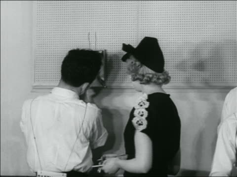 b/w 1936 woman watching young man shaving face in mirror during shaving contest / newsreel - shaving stock videos & royalty-free footage