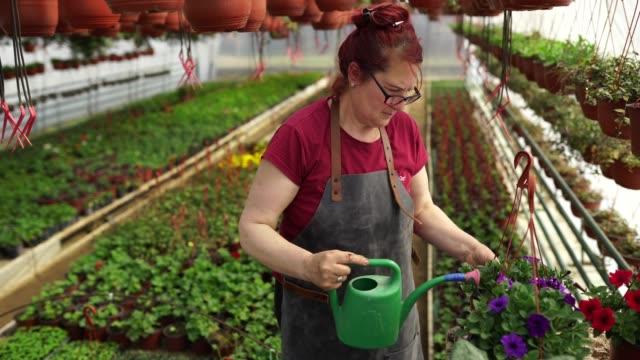 Woman watering flowers in botanical garden
