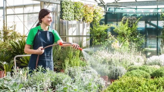 Woman watering plants in garden center