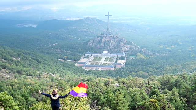 stockvideo's en b-roll-footage met woman waves a flag of the second spanish republic in front of the valle de los caidos mausoleum in san lorenzo del escorial during the exhumation of... - pardo