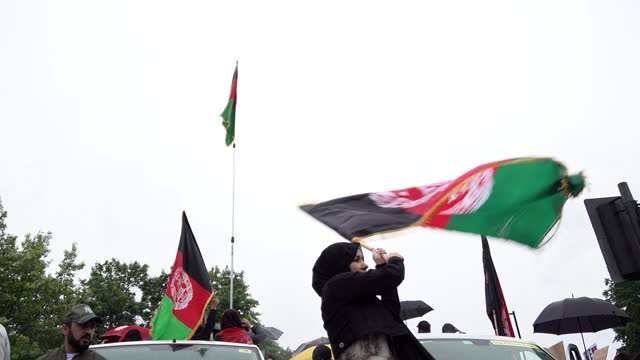 woman waves a large afghan flag as people gather at the start of the free afghanistan, sanction pakistan protest on august 21, 2021 in london, united... - women stock videos & royalty-free footage