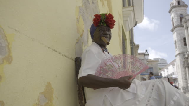 woman waves hand fan and smokes cigar in havana cuba - havana stock videos & royalty-free footage