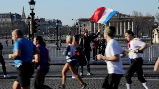 Woman waving a french flag to the runners in front of Palais Bourbon at Place de la Concorde during the sport event Marathon of Paris 2016