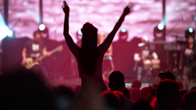 woman waving hands on man's shoulders at concert - musician stock videos & royalty-free footage
