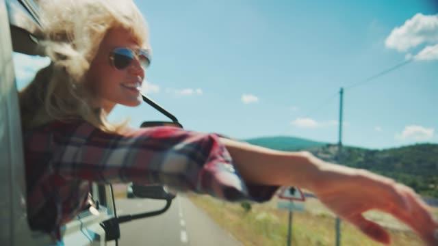 vidéos et rushes de femme agitant des mains hors de la camionnette pendant le jour ensoleillé - évènement public