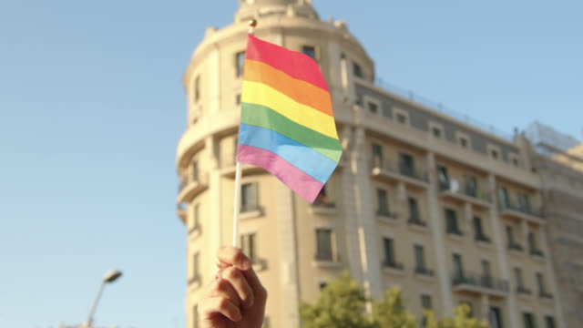 Woman waving little rainbow flag with a building on the background. Barcelona gay pride parade