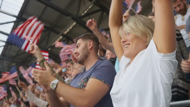 Woman waving the American flag and applauding on the crowded stadium