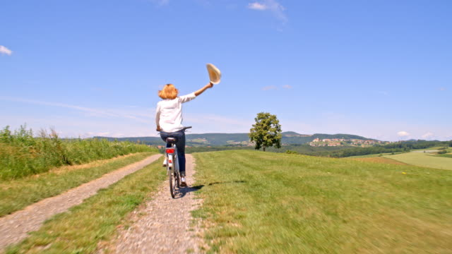 SLO MO Woman waving with her hat while riding a bicycle