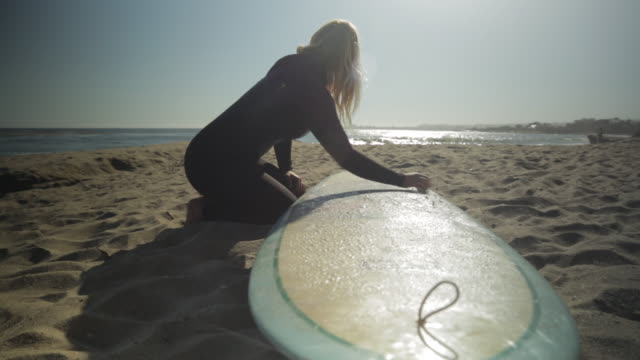 MS DOLLY L-R Woman waxing surfboard