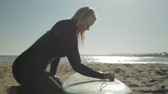 vídeos y material grabado en eventos de stock de ms dolly out woman waxing surfboard, watching waves - tabla de surf