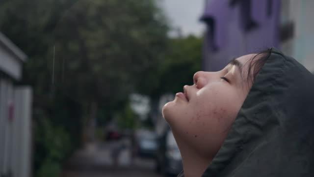 女性はフードを着用し、雨の中で運動します。 - strength点の映像素材/bロール