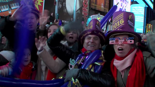 woman wearing 2016 glasses stands with man wearing hat and waves at camera from behind barricade. crowd behind them celebrates in times square after... - times square manhattan stock videos & royalty-free footage