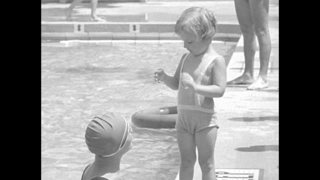 woman wearing a bathing cap in a swimming pool talks with a balky child; she finally gets the girl in the water and the child rides the woman's chest... - backstroke stock videos & royalty-free footage