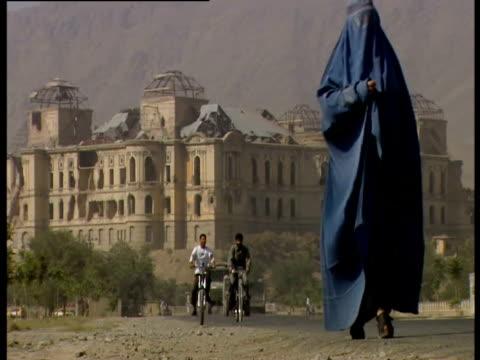 vídeos de stock, filmes e b-roll de a woman wearing a burqa walks along a road in afghanistan - véu