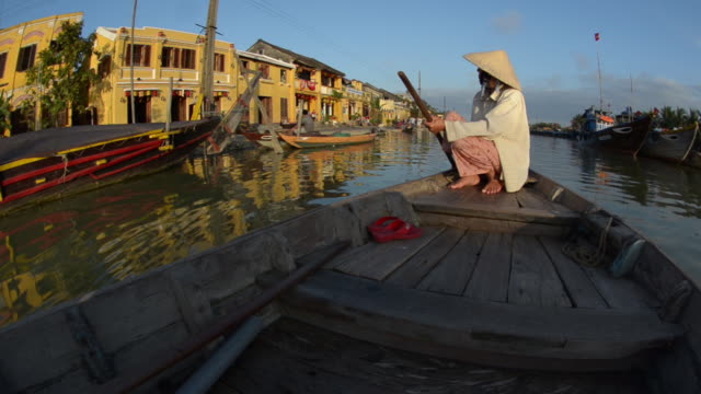 A woman wearing a conical hat rows a boat down the Thu Bon River in Hoi An, Vietnam.