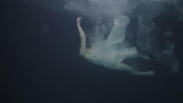 a woman wearing a dress and swimming underwater - 水に飛び込む点の映像素材/bロール