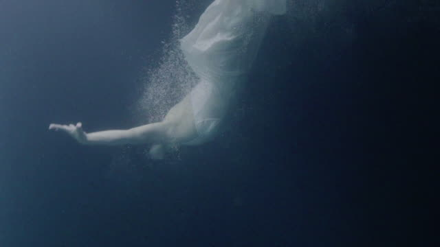 A woman wearing a dress and swimming underwater