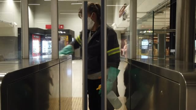 vídeos de stock e filmes b-roll de a woman wearing a face mask cleans and disinfects the train turnstile as the underground trains continues to operate but with a low flow of... - democracia
