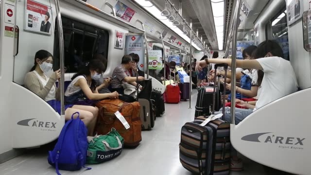 woman wearing a face mask looks at her smartphone as she rides onboard a subway train, a man wearing a face mask looks at his smartphone as he rides... - south korea couple stock videos & royalty-free footage
