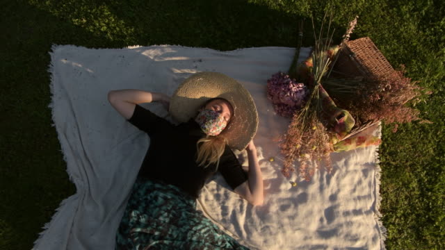 woman wearing a face mask lying on picnic blanket on the grass waves arms - human limb stock videos & royalty-free footage