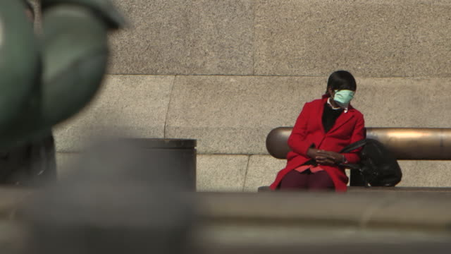 woman wearing a face mask sits on a bench in trafalgar square during the covid-19 pandemic in london, england. - healthcare and medicine or illness or food and drink or fitness or exercise or wellbeing stock videos & royalty-free footage