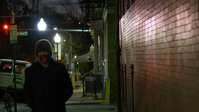woman wearing a face mask walks her dog at night during the coronavirus pandemic on december 7, 2020 in baltimore, maryland. maryland has reported... - district stock videos & royalty-free footage