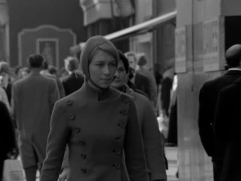 stockvideo's en b-roll-footage met a woman wearing a fitted jacket and a pixie cap walks along a street towards the camera 1967 - kleding