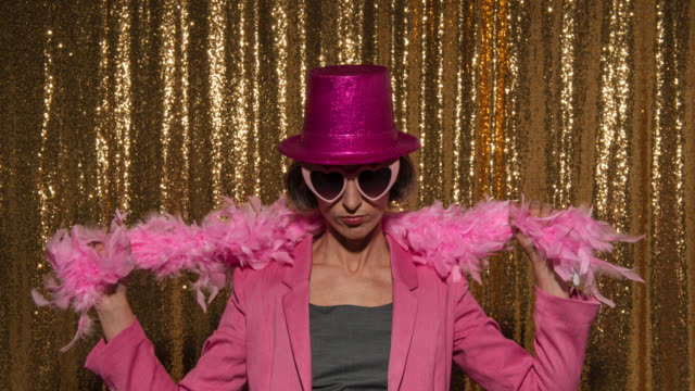 woman wearing a glitter hat and funny props while taking photos in the photo booth at a party - party hat stock videos & royalty-free footage