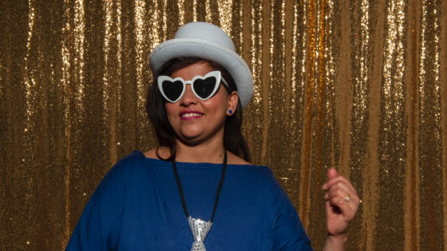 woman wearing a party hat and glasses while taking fun photos in the photo booth - party hat stock videos & royalty-free footage