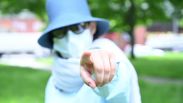 woman wearing a protection mask in a park pointing with her index finger at camera. - index finger stock videos & royalty-free footage