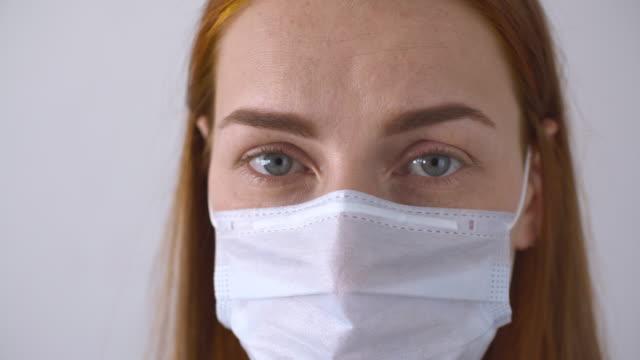 vídeos de stock e filmes b-roll de woman wearing a protective face mask - máscara cirúrgica