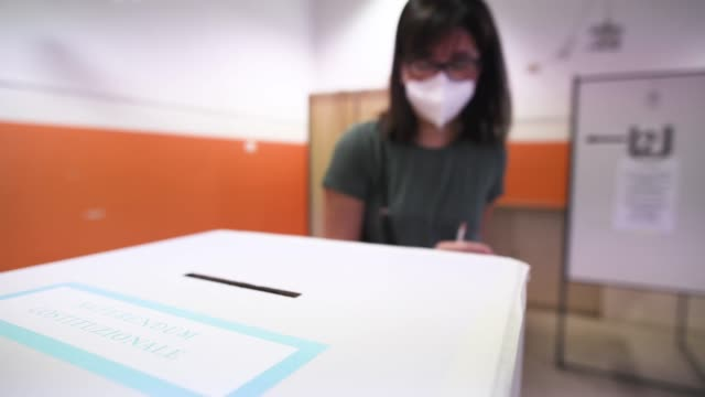 woman wearing a protective mask casts the ballot in the ballot box in the polling station at a school for the vote on the constitutional referendum... - röstsedel bildbanksvideor och videomaterial från bakom kulisserna